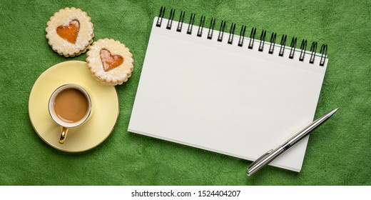 blank spiral art sketchbook against textured green bark paper, flat lay with coffee and heart cookies, love or romance greeting card concept
