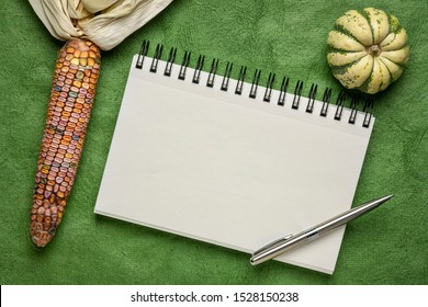 blank spiral art sketchbook against green textured bark paper with ornamental corn and gourd, fall holidays greeting card concept
