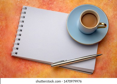 blank spiral art sketchbook with a cup of coffee against textured paper