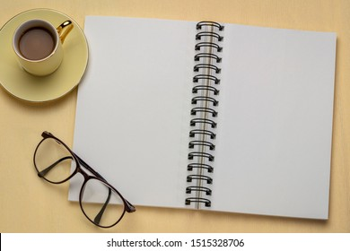 blank spiral art sketchbook with a cup of coffee against textured crepe paper