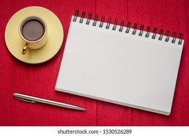blank spiral art sketchbook with a cup of coffee against red textured crepe paper