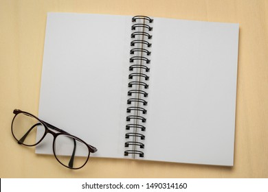 blank spiral art sketchbook with reading glasses against textured crepe paper