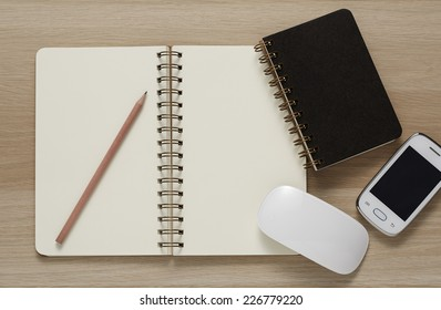 Blank Spiral Note Pad, computer mouse, cellphone and Pencil on Wood Background.