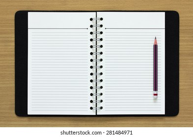 blank spiral notebook and pencil on wood background