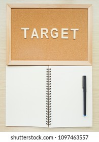 A blank spiral notebook with the reminder wooden board and pen with alphabets TRAGET