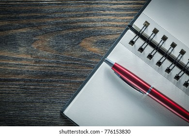 Blank spiral notepad pen on vintage wooden board.