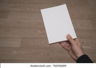 Blank spread, open book in man's hands