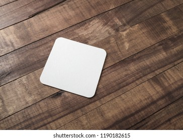 Blank square beer coaster on wooden background.