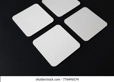 Blank square beer coasters on black paper background. Selective focus.