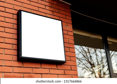 Blank square signboard, business light up sign mock up mounted on the brick wall of a small business workshop store