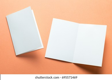 Blank square two-leaf brochures isolated on orange background. Space for text.