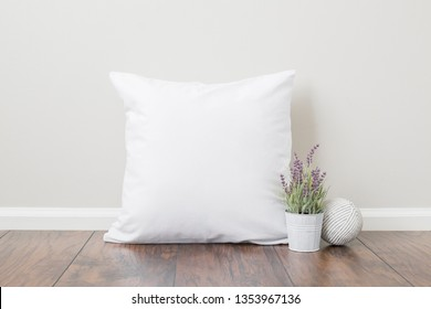 Blank square white pillow sitting on wood floor, mock up