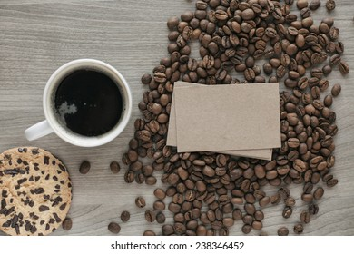 Blank a stack of business cards on coffee beans on a wooden texture with a cup of coffee