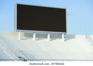 A blank stadium scoreboard screen above the stands in the day time