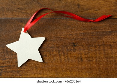 Blank, star-shaped Christmas gift tag with red ribbon on wood background. Simple, country-style, artisanal holiday crafts objects elements.