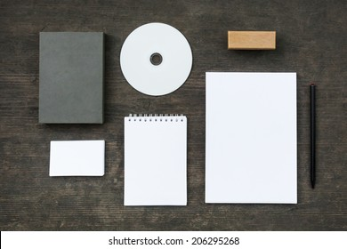 Blank stationery set on old wood background: business cards, booklet, sheets, notebook, stamp, CD, and box. Retro style