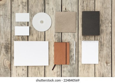 Blank stationery set on old wood background: business cards, booklet, notebook, notepad, CD, box and pen. Vintage style