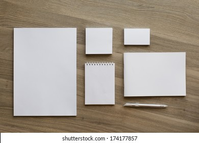 Blank stationery set on wood background / a4 paper, business cards, letterheads, booklet, notepad and pen