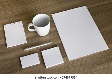 Blank stationery set on wood background / a4 paper, business cards, letterheads, booklet, notepad and cup