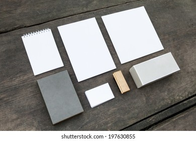 Blank stationery set on wood background: business cards, booklet, sheets, notebook, stamp, and and old boxes (for branded souvenirs).