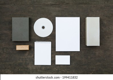 Blank stationery set on wood background: business cards, booklet, sheets, notebook, stamp, CD, and boxes. Retro style
