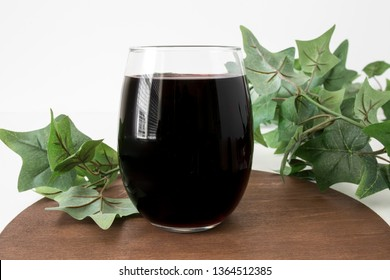 Blank stemless wine glass filled with red wine on wood with vines, drinkware mock up