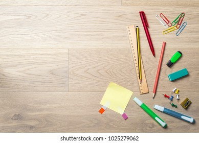 Blank sticky note with copy space and free space for writing a message lying on office desk with pen, pencil, highlighter and ruler as flat lay from bird's eye view