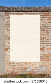 blank street advertising billboard glued on brick wall - empty white poster,sheet of paper, copy space