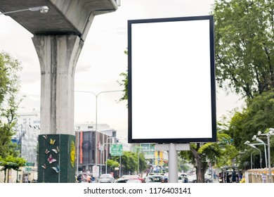 blank street billboard in urban road city area with skytrain rail line in the background , isolated empty advertisement display for design
