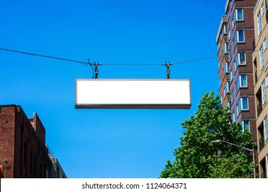 Blank street sign hanging over an avenue. Mockup and commercial concept.