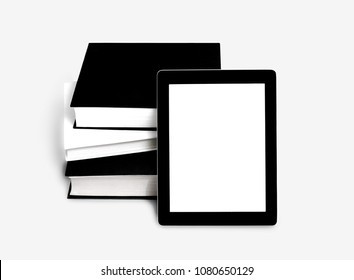 Blank tablet or e-book and pile of old books over gray background