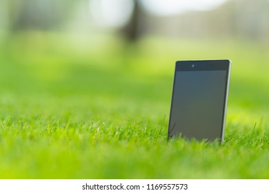 Blank tablet pc with a black screen with copy space standing upright in green grass in a low angle view