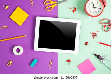 Blank tablet with school and office supplies on colorful office table.