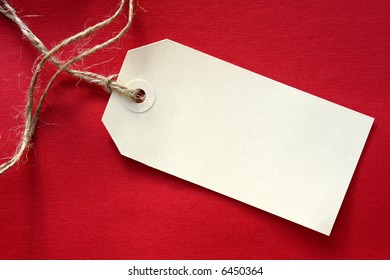 Blank tag tied with string, on vibrant red textured background.