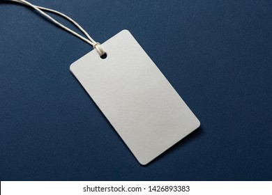 Blank tag tied with string. Price tag, gift tag, sale tag, address label isolated on blue background - Shutterstock ID 1426893383