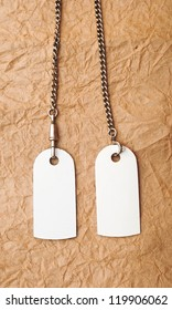 blank tags with silver chain on vintage background. space for your text
