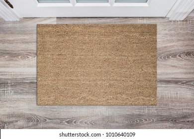 Blank tan colored coir doormat before the white door in the hall. Mat on wooden floor, product Mockup