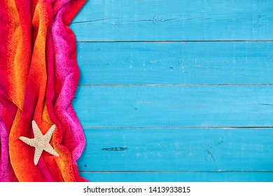 Blank teal blue wood sign with red and pink beach towel and starfish border; vacation background with copy space