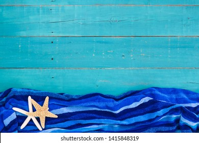 Blank teal blue wood sign with beach towel and starfish border; vacation background with copy space