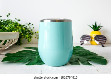 Blank teal wine tumbler on white background with palm leaves, sublimation insulated drinkware, summer mockup