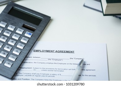 Blank template for an Employment Agreement with pen and calculator on a white desk ready to be negotiated and signed