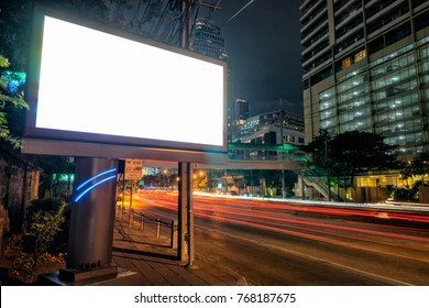 Blank template for outdoor advertising or blank billboard with light trail to business district in twilight. With clipping path on screen - can used for trade shows, advertising or promotional poster.