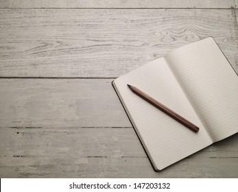 Blank textbook on white hardwood desk. Shot with smart phone.