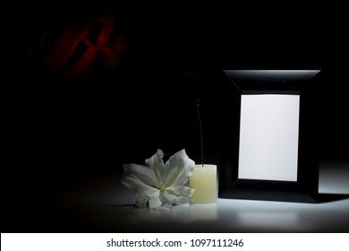 Blank thich black picture frame, with smoky candle and white lily flower on dark background with red decoration