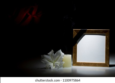 Blank thin brown picture  frame, with smoky candle and white lily flower on dark background with red decoration