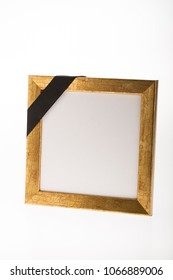 blank thin gold mourning picture frame with black ribbon  on bright background for obituary card