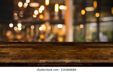 Blank top wooden bar counter with blur cafe background and night pub of restaurant, cafeteria background. Using for Mock up template for craft display of your design,Banner for advertise of product.