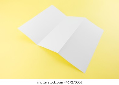 blank trifold white template paper on yellow background with soft