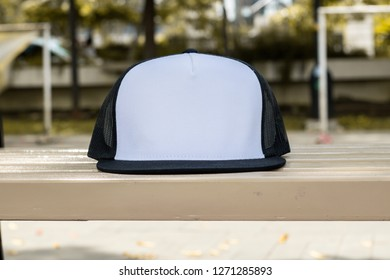 Blank trucker hat cap flat visor with black and white color in outdoor, ready for your mock up design or presentation your design project