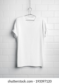 Blank t-shirt hanging on white wall